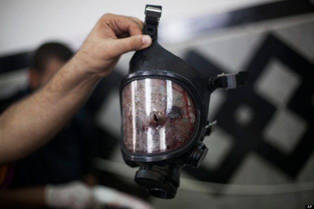 A bullet hole is seen in the front of a gas mask belonging to a supporter of ousted Egyptian President Mohammed Morsi in Cairo's Nasr City district, Egypt, Wednesday, Aug. 14, 2013. Egyptian police in riot gear swept in with armored vehicles and bulldozers Wednesday to clear two sprawling encampments of supporters of the country's ousted Islamist president in Cairo, showering protesters with tear gas as the sound of gunfire rang out. (AP Photo/Manu Brabo)