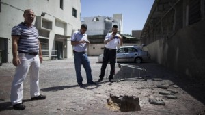 Israelis look at a crater caused by a rocket outside a shop in Ashdod, on the second day of Operation Protective Edge, Wednesday, July 9, 2014 (photo credit: Yonatan Sindel/Flash90