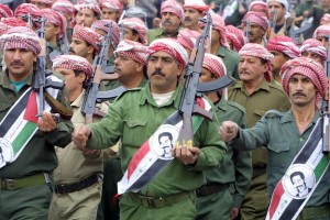 BAGHDAD, IRAQ:  Members of the ruling Baath party parade with kalashnikovs and portraits of Iraqi President Saddam Hussein on Iraqi flags in Baghdad 08 February 2002 during celebrations marking the 39th anniversary of the 1963 coup that brought the party to power.       AFP PHOTO/Ramzi HAIDAR (Photo credit should read RAMZI HAIDAR/AFP/Getty Images)