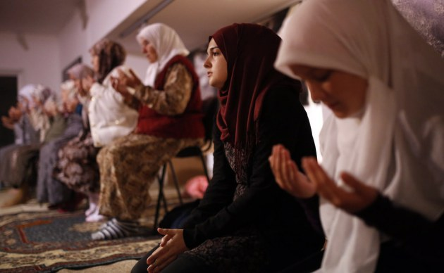 Bosnian Muslims offer a prayer during late night prayer for upcoming holy month of Ramadan, inside memorial room for Srebrenica massacre victims, at the memorial center Potocari, northeast of the Bosnian capital of Sarajevo. Family members of the Srebrenica victims killed in July, 1995, will mark the first night of Ramadan at the memorial center Potocari, in front of the graves of killed Muslims from this small Bosnian town. Amel Emric / AP