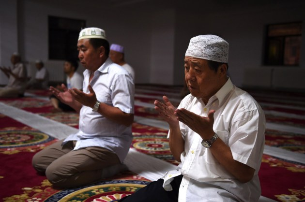 Muslims pray after breaking their fast on the first day of Ramadan, the muslim holy month, at a mosque in Beijing. China has banned civil servants, students and teachers in its mainly Muslim Xinjiang region from fasting during Ramadan and ordered restaurants to stay open. Greg Baker / AFP / Getty Images