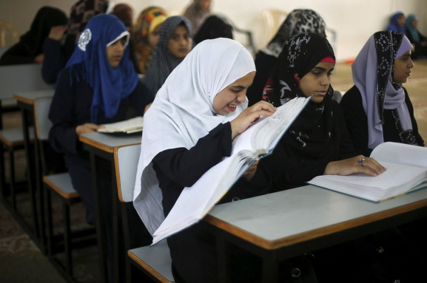 Blind and visually impaired Palestinian girls read the Braille version of the Qur'an during a Qur'an memorization class at the main center of Dar al-Quran Society, on the first day of the holy month of Ramadan in Gaza City. Thousands of Palestinians, among them blind and visually impaired students, are taking lessons which are sponsored by the Muslim organization Dar al-Quran Society. The society teaches people the right recitation of the Muslim holy book and helps them memorize the whole Qur'an, directors in the organization said. Suhaib Salem / Reuters